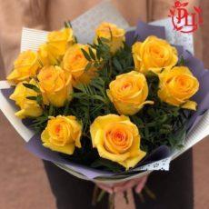 букет из 11 желтых роз с зеленью в упаковке